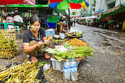 12 JUNE 2013 - YANGON, MYANMAR:    A woman sorts her vegetables in a market stall during a thunderstorm in Yangon, Myanmar.      PHOTO BY JACK KURTZ