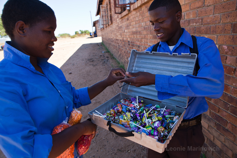 18 March 2011, Mmaphuti Secondary School, Capricorn District, Kalkspruit, South Africa. Lesley Galane (16) a student in Grade 9, on the right, sells sweets to fellow students to earn up to R150 a week in additional pocket money. R1 for a lollipop and 20 cents per sweet. The Girls and Boys education movement provides African children a platform to make the best of their potential. It gives them access to skills and information, helps them to mobilise their communities to support the rights of girls and provides a space where they can discuss issues that matter to them.