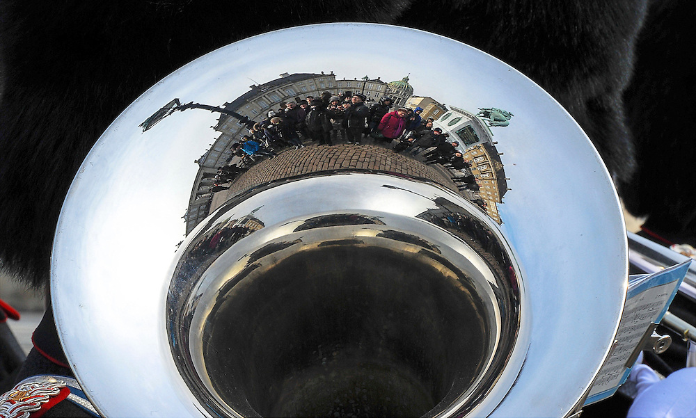 Every day outside the Danish palace of Amalienborg Slot in Copenhagen, tourists from around the world gather to try and catch a glimpse of the royal family or the changing of the guard ceremony. They are seen here reflected in the trombone of one of the guards.