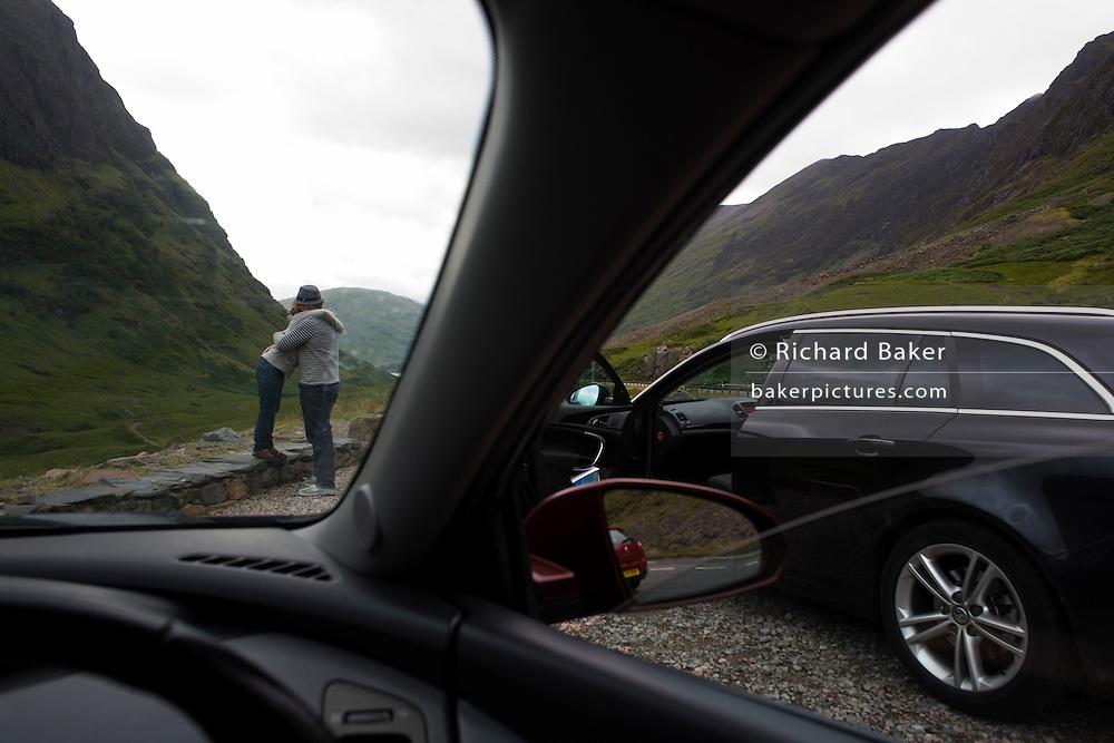Couple's spontaneous hug during stopped car journey through Glencoe, Scotland.