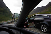 Couple's spontaneous hug during stopped car journey through Glencoe, Scotland.