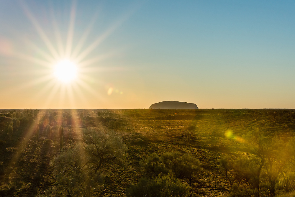 Sunrise at Uluru with clear sky and sun flare