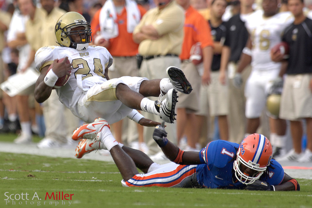 Sept. 9, 2006; Gainesville, FL, USA;  Central Florida Golden Knights running back Kevin Smith is tripped up by Florida Gators defender Reggie Nelson in the first quarter at Ben Hill Griffin Stadium. ...©2006 Scott A. Miller