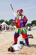 Tewkesbury, Gloucester UK July 201 : Jimmy Juggle the Jester & two children volunteers mid juggling act, Tewkesbury Medival Festival