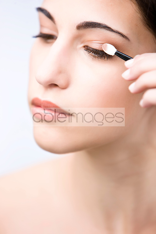 Profile up of a young woman applying eyeshadow - close up