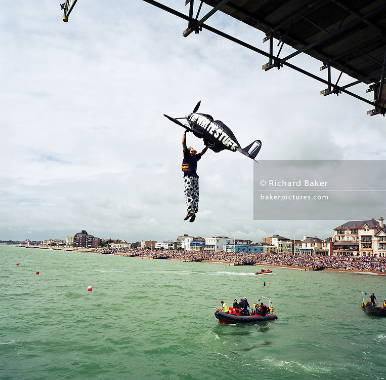A competitor in the annual Birdman of Bognor event attempts to fly at Bognor Regis, East Sussex, England. English eccentrics gather annually at the southern seaside town to jump from the pier into the chilly waters of the English Channel. Fun jumpers ?wearing? their aeroplane suits compete for a £25,000 prize for the one to fly 100 metres from the pier platform ? a record not yet achieved. Entrants (who often jump for charity rather than any aeronautical pretensions) include sugar plum fairies, condoms, Ninja Turtles and vampires. The winner was a hang-glider pilot reaching 26 metres but here, a Spitfire sponsored by a milk company drops vertically. Picture from the 'Plane Pictures' project, a celebration of aviation aesthetics and flying culture, 100 years after the Wright brothers first 12 seconds/120 feet powered flight at Kitty Hawk,1903. .