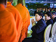 20 JANUARY 2017 - BANGKOK, THAILAND: Pol Gen ASWIN KWANMUANG, (right) the Governor of Bangkok, greets Buddhist monks filing into a merit making ceremony on the plaza in front of Bangkok's City Hall. Hundreds of municipal workers and civil servants made merit by praying and presenting alms to 89 Buddhist monks Friday to mark 100 days of mourning since the death of revered Bhumibol Adulyadej, the Late King of Thailand. The significance of 89 monks is that the King, who died on October 13, 2016, was a few weeks short of his 89th birthday.        PHOTO BY JACK KURTZ