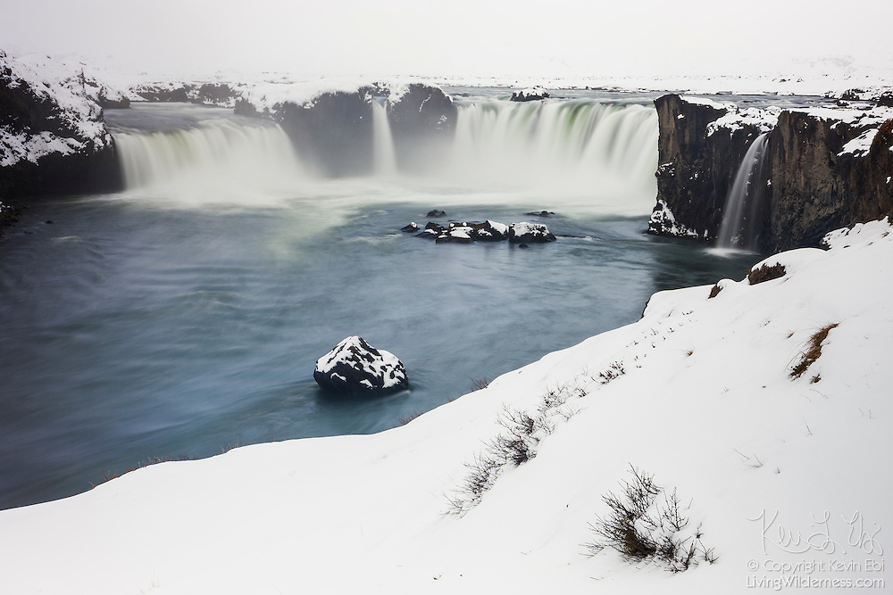 "Heavy snow blankets the banks of Goðafoss, regarded one of the most spectacular waterfalls in Iceland. The name Goðafoss means ""Waterfall of the Gods."" Located near Mývatn, it plunges 12 meters and is more than 30 meters wide, and is the largest waterfall on the Skjálfandafljót river. The name, however, comes from Icelandic legend: in the year 1000 AD, Þorgeir Ljósvetningagoði, a chieftain in the region, threw his statues of the pagan gods into Goðafoss when he decided Icelanders should adopt Christianity."