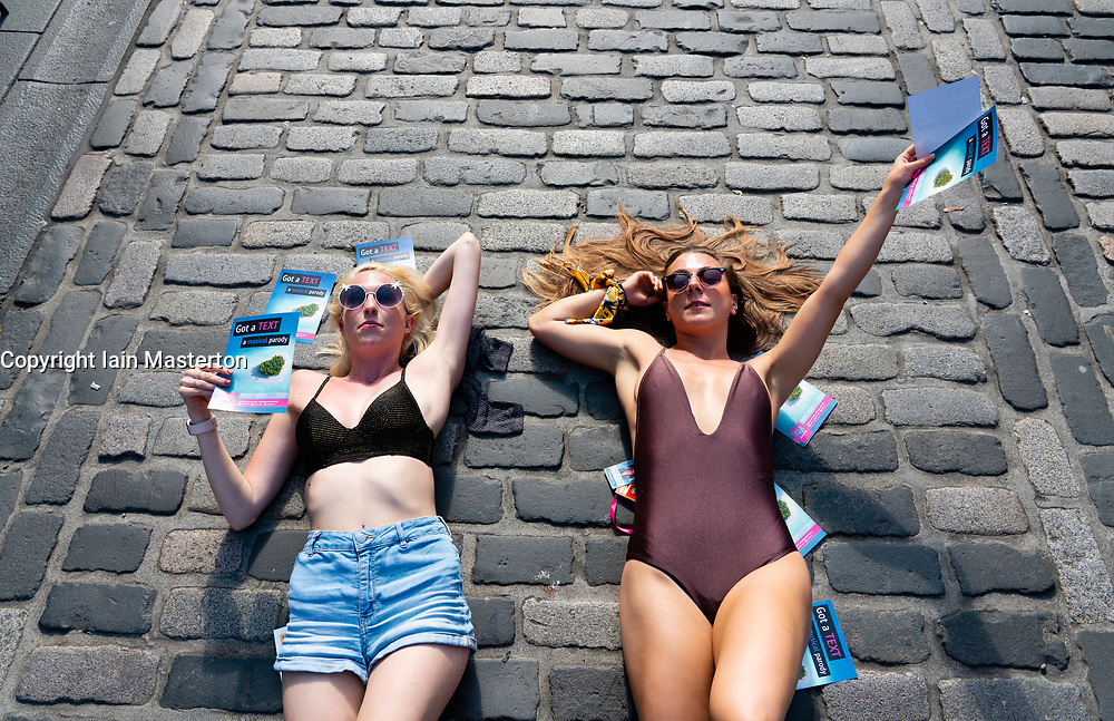 Edinburgh, Scotland, UK. 2 August 2019. On the opening day of the Edinburgh Festival Fringe these two young women were sunbathing on the Royal Mile and handing out flyers to their show Got a Text: A Musical Parody