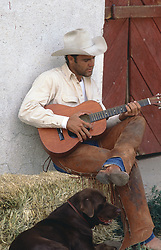 good looking cowboy playing his guitar while a chocolate lab dog sits by his feet on a ranch in New Mexico