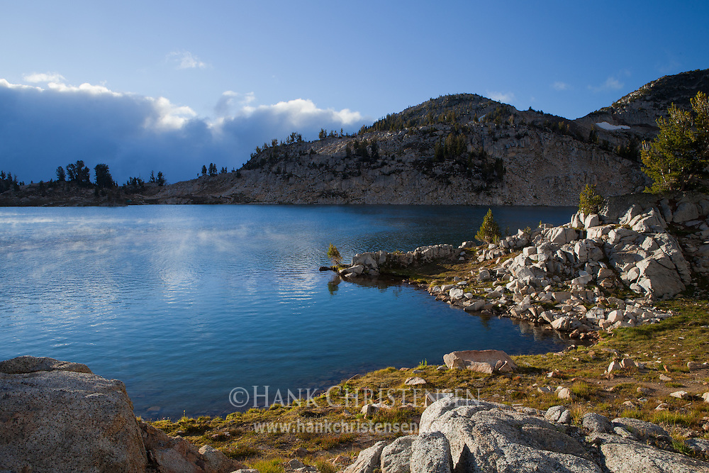 The first rays of sunlight heat the cold waters of Glacier Lake, creating steam, Eagle Cap Wilderness, Oregon