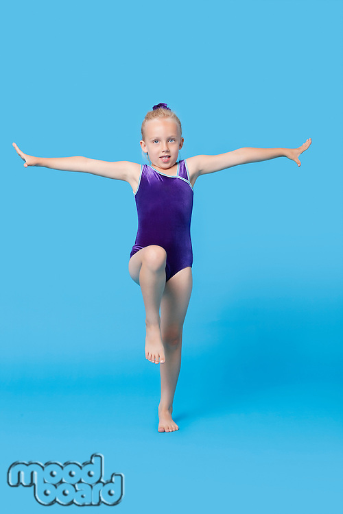 Portrait of a young female gymnast performing over blue background