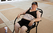 """Shelly Wright is third in line with """"Pick Me"""" and her phone number written on her belly for casting for season 11 of """"The Biggest Loser"""" television show in Broomfield, Colorado July 17, 2010. Wright spent the night on the sidewalk outside the hall for a chance to be on the show and win $250,000.  Over 600 people attended the casting call.   REUTERS/Rick Wilking (UNITED STATES)"""
