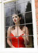 Young woman in an orange, strapless evening dress, looking through a leaded window.