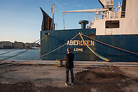 """TRAPANI, ITALY - 7 JUNE 2016: A marshal of the Guardia di Finanza (Financial Police) stands by the cargo ship Aberdeen, seized in June 2014 as it was carrying 42 tons of hashish from Morocco to Libya, is docked here in the harbor in Trapani, Italy, on June 7th 2016.<br /> <br /> Between January 2014 e December 2015 more than 120 tons of hashish, carried on fishing boats or cargo ships from Morocco to Libya, were seized in the Strait of Sicily by Italy's Guardia di Finanza (Financial Police) thanks to an international police investigation named """"Operazione Libeccio"""", carried out by the GICO (Gruppo Investigativo Criminalità Organizzata, Organised Crime Investigation Group), a unit of the tax police of Palermo under the supervision of the DDA (Direzione Distrettuale Antimafia) of Palermo.<br /> <br /> """"What is happening in Libya is same historical occurrence that happened years ago in Afghanistan. Such as the Talibans who financed their terroristic activities with heroin trafficking for the purchase of weapons, the Caliphate is proposing the same terroristic strategy by purchasing and commercialising hashish in order to purchase weapons used in their war"""" Sergio Barbera, Deputy General Prosecutor of Palermo, said."""