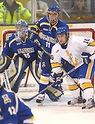 UAF's Joe Sova (11) tries to keep LSSU's Chad Nehring (16) away from Nanooks goalie Scott Greenham (35) during Alaskas Saturday night win over LSSU.