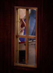 © Licensed to London News Pictures. 14/01/2017. London, UK. Labour Party leader JEREMY CORBYN seen through a window waiting to speak at the Fabian Society conference in London on January 14, 2016. Corbyn has come under further pressure as leader following the resignation of Stoke-on-Trent, Tristram Hunt. Photo credit: Ben Cawthra/LNP