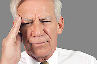 Close-up of a businessman suffering from headache over gray background