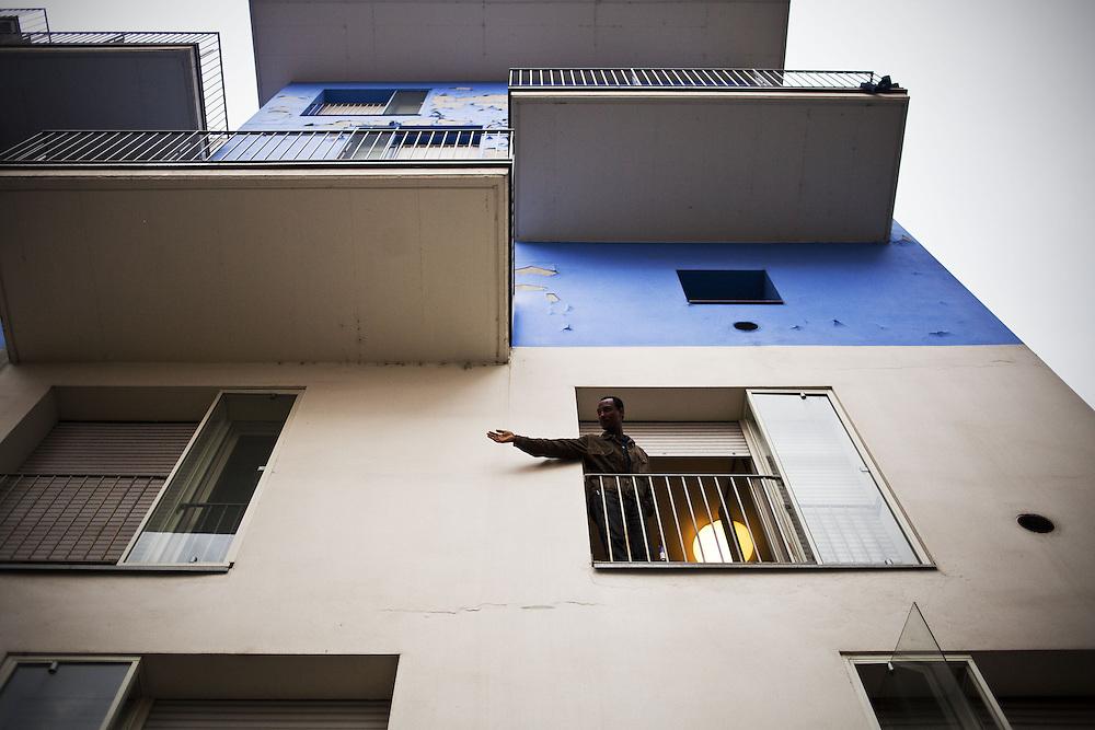 Un ragazzo si affaccia dalla finestra di una delle ex palazzine olimpiche.