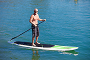 Fit And Active Senior Man Paddleboarding