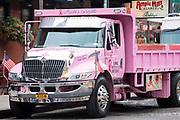 Bright pink builders' truck painted In Loving Memory of Linda - Linda's Angels in New York City, USA