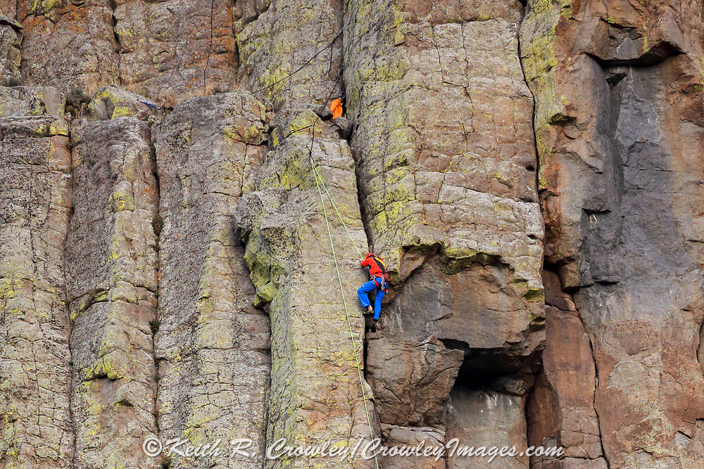 A rock climber ascends the side of Devils Tower