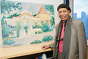 NEW YORK - March 27: Painter Eric Girault with one of his Gingerbread paintings at FOKAL's The Promise of Haiti II Event. Photographed March 27, 2015 at the Medici Group in NY, NY. 2015 © Cat Laine.