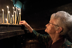 """3 June 2018, Novi Sad, Serbia: A congregant lights a candle to pray as they await Sunday service in the Eastern Orthodox Cathedral Church of the Holy Great Martyr George. On 31 May - 6 June 2018, in Novi Sad, Serbia, the Serbian Orthodox Church stood as one of the host churches of the Conference of European Churches General Assembly. More than 400 delegates, advisors, stewards, youth, staff, and distinguished guests took part in the Assembly and related events, gathered under the theme, """"You shall be my witnesses""""."""