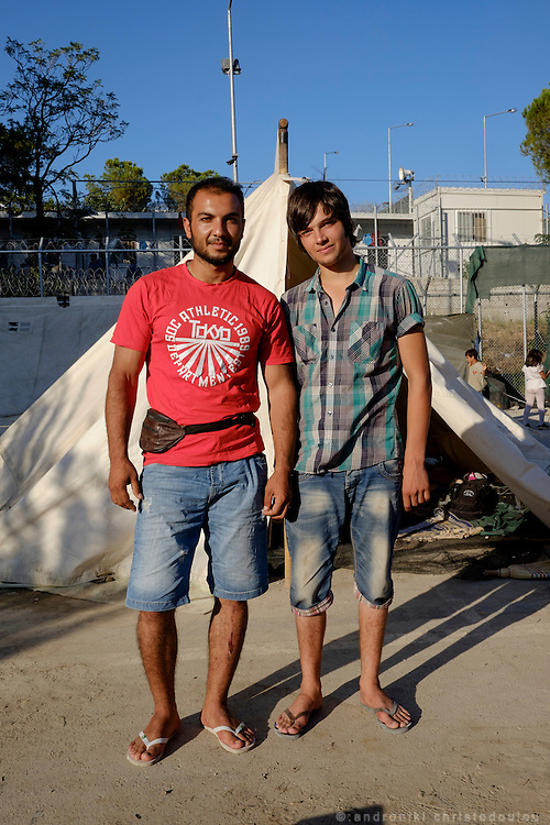 Rahmatullah (24, on the left) is travelling together with his middle brother Aziz (21, on the right). He is fluent in English as he used to work as a translator for the American army. He left Afghanistan once and lived in the US for two years until he was asked to leave the country because of a fight he had had with a US solder in Afghanistan. He said that what happened was that he stopped the US solder when he entered a house and tried to rape a young Afghani mother. He had to return to Afghanistan. He stayed there for two years but he often received threats because Afghanis saw him as someone who had collaborated with the &ldquo;infidel&rdquo;. Six months ago they attacked and injured his younger brother with a hand-grenade, mistaking him for Rahmatullah. He and his brother Aziz left Afghanistan 45 days ago and crossed to Greece via Turkey. Their final destination is Denmark where they already have members of their family living there. <br /> Moria refugee camp is a bit further out of Mytilene city and it is divided in two sections. The inner part is well organised with buildings and police guarding it, and the outer part where mainly Afghan refugees live in tents and is purely guarded with chaotic situations, mainly during food distribution, frequently occur.