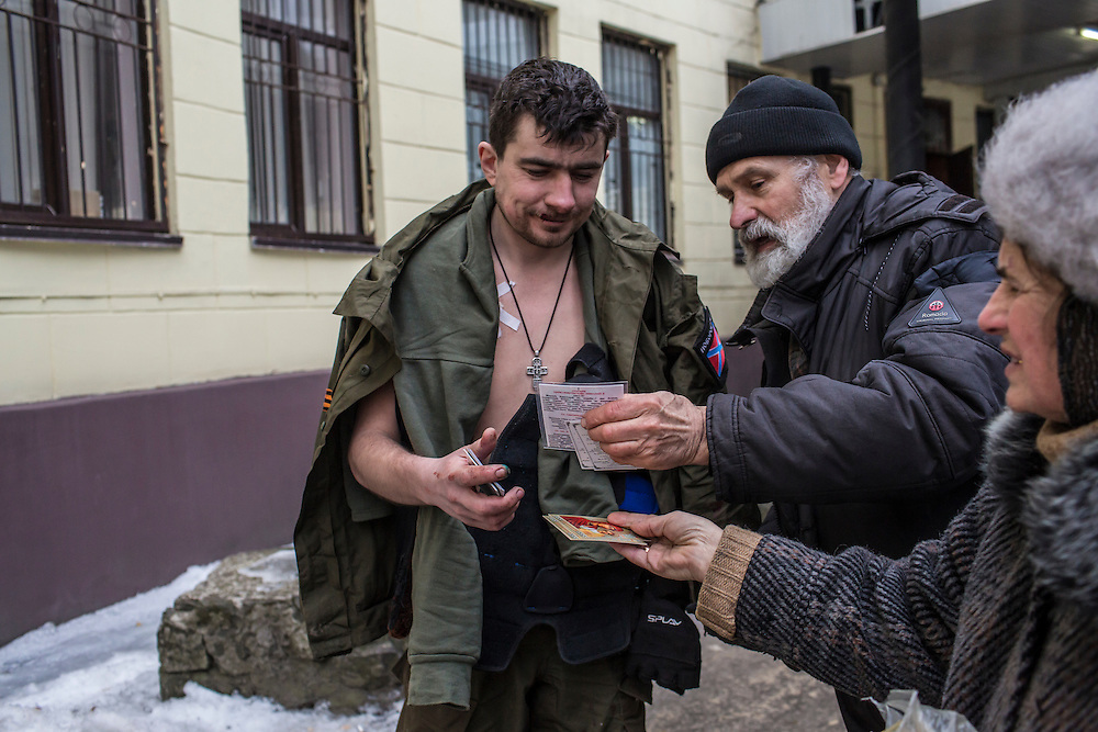 DONETSK, UKRAINE - JANUARY 26, 2015: A wounded rebel fighter is given Orthodox religious icons outside Vishnevskogo Hospital in Donetsk, Ukraine. Heavy fighting in recent days has killed dozens of people. CREDIT: Brendan Hoffman for The New York Times