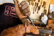 Men make wooden carvings at the Village Artisanal de Ouagadougou, a cooperative that employs dozens of artisans who work in different mediums, in Ouagadougou, Burkina Faso, on Monday November 3, 2008.