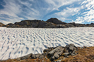 Remnant snowfield at Thompson Pass near Valdez in Southcentral Alaska. Summer. Afternoon.