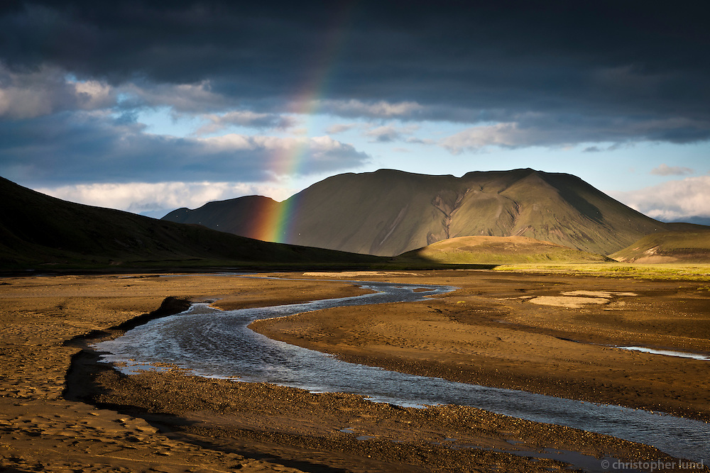 Evening at Fjallabak Nature Reserve, Interior of Iceland. Small stream near Landmannahellir, a rainbow glows in evening light over Mount Lifrarfjöll.