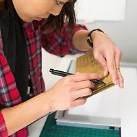 Joyce Li measures where the polymer plate will line up on the invitation she has designed at the print workshop for The Onyx Press in Amory. Li said that she had to learn a lot when she first got the press two years ago, but there has been an online community that has been very helpful.