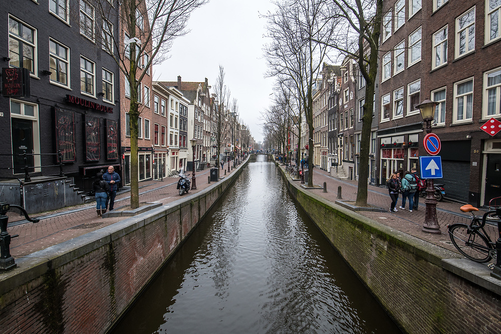 A canal runs through the peaceful city of Amsterdam  with iconic canal hoses lining either side, Netherlands.