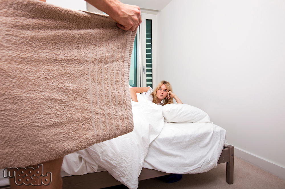 Woman looking at nude man holding towel in bedroom