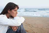 Pensive Woman on the Beach looking out to sea side view close up