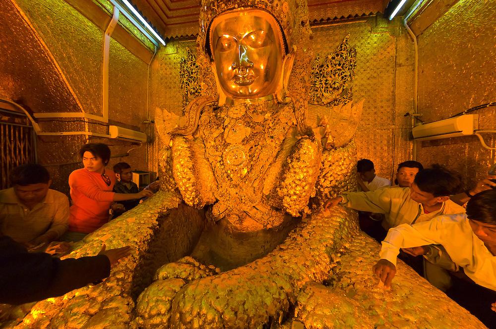 People putting Gold leaf on the Maha Muni Buddha, Mandalay, Myanmar (Burma)