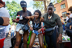 © Licensed to London News Pictures. 29/08/2016. London, UK. A drunk woman is being helped by her friends on the second day of Notting Hill Carnival in west London, Monday 29 August 2016. Photo credit: Tolga Akmen/LNP