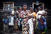 "Jeanne Kahindo, 35, stands in front of her home with her children and the  12 displaced people she shelters in Goma, Eastern Democratic Republic of Congo on Sunday December 14, 2008. All of them come from Kibumba, 40km north of Goma, and have been living with Kahindo for two months. ""The people were suffering, under the rain, that's why I offered them to come in"", she says. She explains that when someone finds something to eat they bring it back to share it with others. Is it estimated that only 30% of the displaced people in Eastern DRC have found refuge in organized IDP camps. The rest are living in schools, churches, or with host families..."