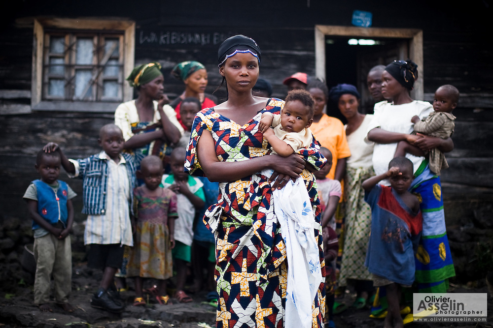 """Jeanne Kahindo, 35, stands in front of her home with her children and the  12 displaced people she shelters in Goma, Eastern Democratic Republic of Congo on Sunday December 14, 2008. All of them come from Kibumba, 40km north of Goma, and have been living with Kahindo for two months. """"The people were suffering, under the rain, that's why I offered them to come in"""", she says. She explains that when someone finds something to eat they bring it back to share it with others. Is it estimated that only 30% of the displaced people in Eastern DRC have found refuge in organized IDP camps. The rest are living in schools, churches, or with host families..."""