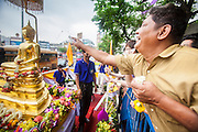 12 APRIL 2013 - BANGKOK, THAILAND:   . Thais sprinkle scented oils on the Phra Buddha Sihing while it is paraded through the streets of Bangkok on the first day of Songrkran. The Phra Buddha Sihing, a revered statue of the Buddha, is carried by truck through the streets of Bangkok so people can make offerings and bathe it in scented oils. Songkran is celebrated in Thailand as the traditional New Year's Day from 13 to 16 April. The date of the festival was originally set by astrological calculation, but it is now fixed. If the days fall on a weekend, the missed days are taken on the weekdays immediately following. Songkran is in the hottest time of the year in Thailand, at the end of the dry season and provides an excuse for people to cool off in friendly water fights that take place throughout the country. The traditional Thai New Year has been a national holiday since 1940, when Thailand moved the first day of the year to January 1. The first day of the holiday period is generally the most devout and many people go to temples to make merit and offer prayers for the new year. PHOTO BY JACK KURTZ