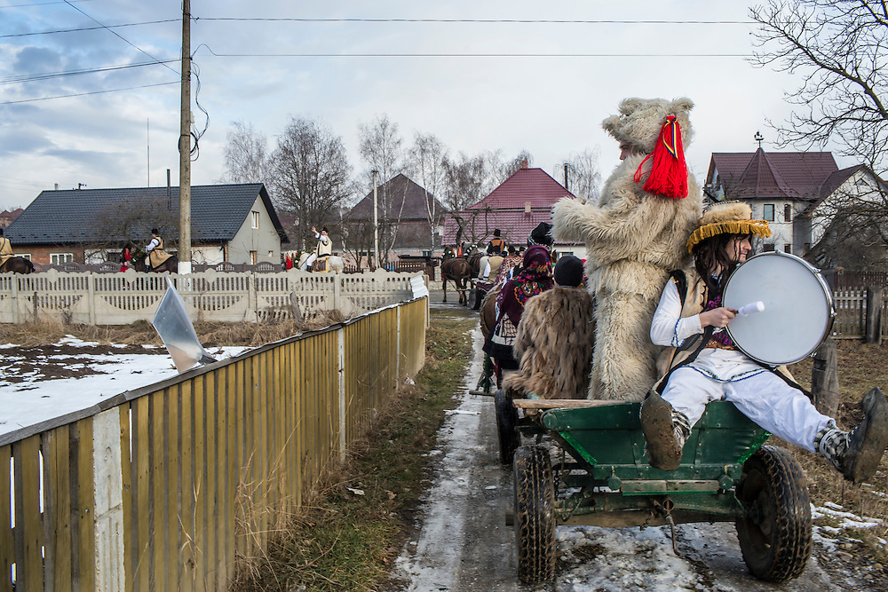 Vasyl Pruzha, in the bear costume, and his cousin Mykola Pruzha, with drum, along with other people from their district, go from house to house singing carols on Wednesday, January 13, 2016 in Krasnoilsk, Ukraine. The tradition, separate from Malanka, coincides with the New Year according to the Orthodox calendar.