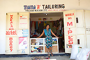 "Rahab Mbuba outside her shop front.<br /> <br /> Rahab, also known as 'Mama B"", set up and now runs a tailoring business, designing and making clothes.<br /> <br /> She attended MKUBWA enterprise training run by the Tanzania Gatsby Trust in partnership with The Cherie Blair Foundation for Women."