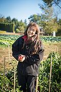 Shari Sirkin holding red pepper on Dancing Roots Farm.