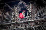 A Hindu holy man looking out from a Newari style wooden temple in Kathmandu, Nepal.