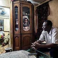 25/07/2014. Conakry. Guinée Conakry. Bidonville de Coronthie. Meloude Fall, mari de Fatoumata regarde la télévision dans son salon. ©Sylvain Cherkaoui/Cosmos pour M le magazine du Monde