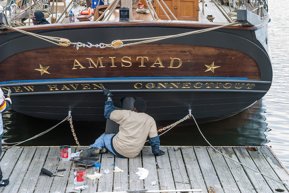 Black boatyard worker touches up the transom paint on the former slave and sailing vessel Amistad tied up at dock