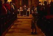 A child plays in the aisle as Mass is being held in a local rural Catholic church, on 15th October 1997, in Neubourg, Normandy, France