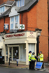 © Licensed to London News Pictures. 17/04/2012. Weybridge, UK . Police officers at the scene. The man is believed to have died in a flat above a pharmacy. A man in his 20s has been arrested on suspicion of murder after the death of a man in his 40s from a stab wound at a house in Surrey. Police said officers were called to an address in Queen's Road, Weybridge by South East Coast Ambulance Service just before 17:00 BST. Photo credit : Stephen Simpson/LNP